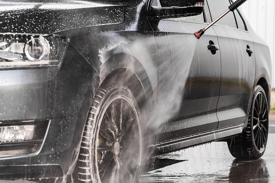 Car Wash Insurance - Closeup of a Black Sedan Car Being Power Washed
