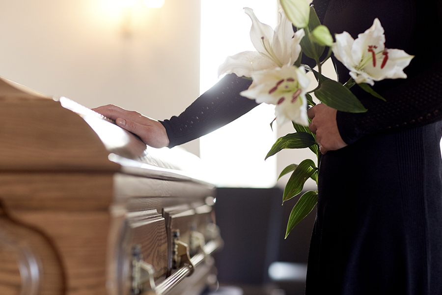 Funeral Home Insurance - Closeup of Woman With Flowers Placing a Hand on a Casket