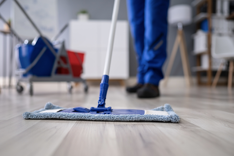 Janitorial and Cleaning Service Bonds - Closeup of Janitor Cleaning the Floor of an Office