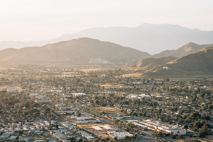 Riverside, CA - Aerial View of a Riverside County City in California at Sunset With Community and Mountains in the Background