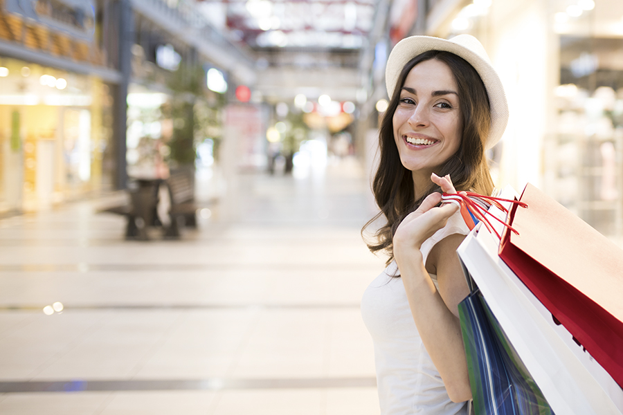 Shopping Center Insurance - View of a Woman Shopping and Holding Bags Over Her Shoulder in a Mall With Stores in the Background and Blurred