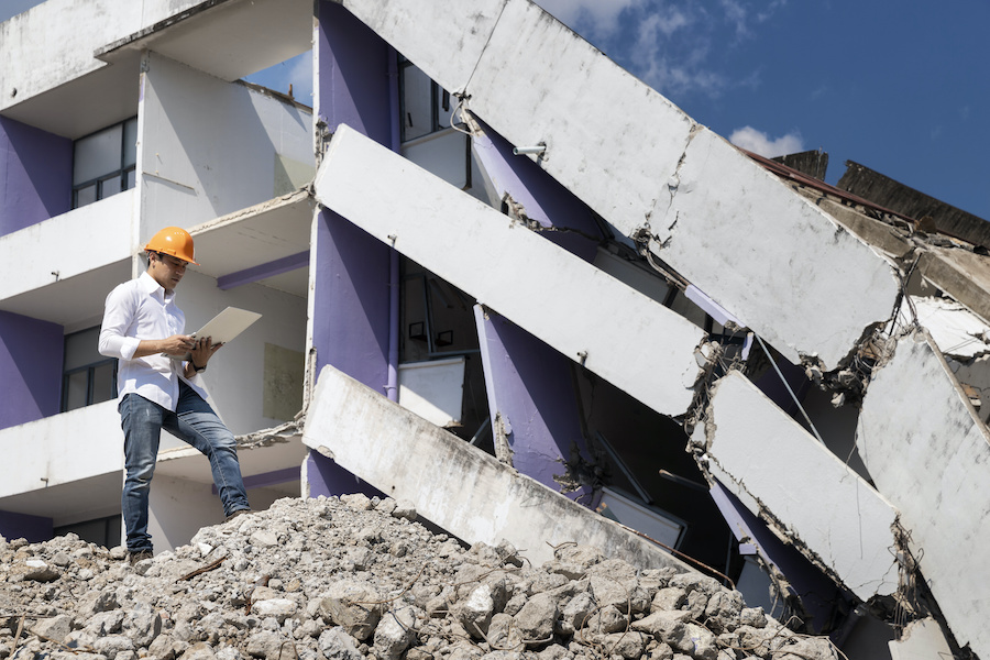Commercial-Earthquake-Insurance-Engineer holding laptop is checking for destruction, demolishing building.